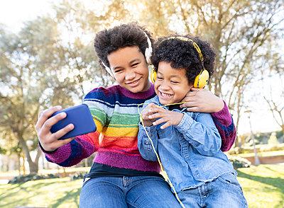 Sibling wearing headphones smiling while taking selfie through mobile phone while sitting at park - p300m2252647 by Jose Carlos Ichiro