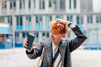 Redhead man with hand in hair taking selfie on smart phone outdoors - p300m2267849 by Oxana Guryanova