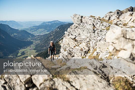 Junger Wanderer auf steinigem Bergweg - p1142m2056565 von Runar Lind
