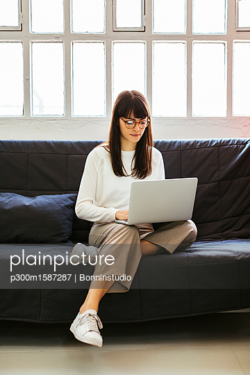 Young woman sitting on couch in office using laptop - p300m1587287 von Bonninstudio