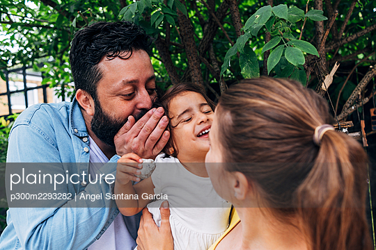 Father whispering in ear of daughter while playing with mother at back yard - p300m2293282 by Angel Santana Garcia