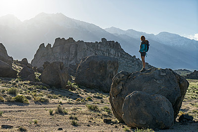 Full length of female hiker looking at Alabama Hills while standing on rock - p1166m1473990 by Cavan Images