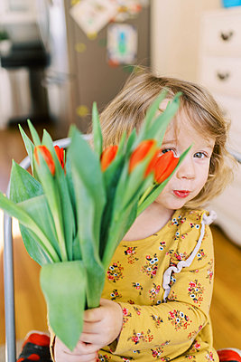 Little two year old girl holding a bunch of tulips. - p1166m2162801 by Cavan Images