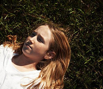 Rothaariges Mädchen liegt entspannt im Gras - p1577m2220075 von zhenikeyev
