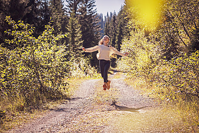Girl running and jumping on a forest path, having fun - p300m2166380 by Studio 27