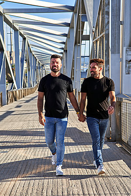 Happy homosexual couple holding hands while walking on bridge - p300m2226766 by Veam