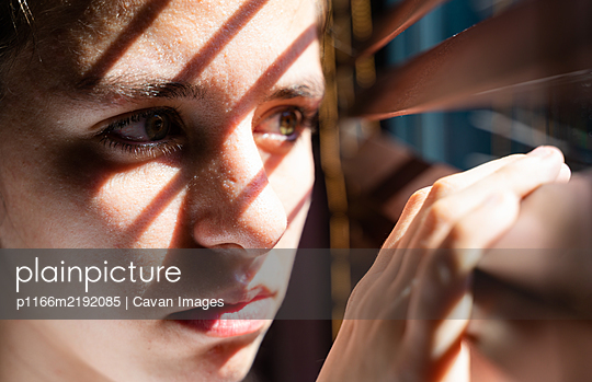 youth girl with green eyes opening a wooden curtain with her fingers to look through the window while the sunlight creates sun and shadow on her face that shows hopeless. Horizontal photo - p1166m2192085 by Cavan Images