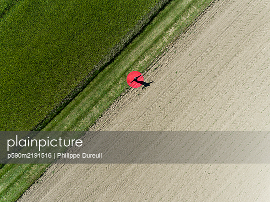 Man standing on red dot between two Fields View from above - p590m2191516 von Philippe Dureuil
