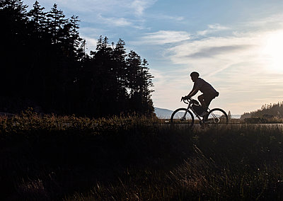 cyclist rides bike along road in Acadia National park, Maine - p1166m2208021 by Cavan Images