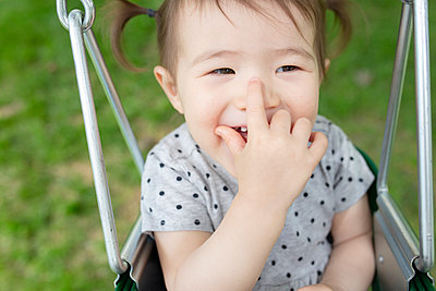 Adorable Baby Girl Smiles with Hand Over Mouth While Swinging Outdoors - p1166m2218367 by Cavan Images