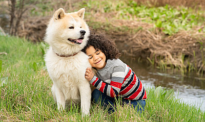 Smiling boy leaning on dog while sitting on grass in nature - p300m2265864 by Jose Carlos Ichiro