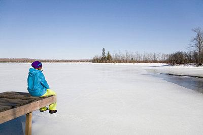 Woman Relaxing on Dock by Frozen Lake - p4295755 by Hugh Whitaker