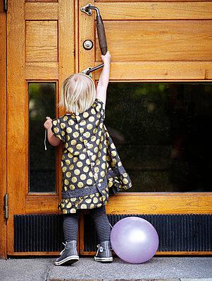 Scandinavia, Sweden, Stockholm, Girl opening door, rear view - p5282276 by Anna Kern