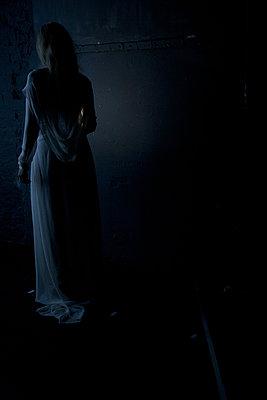 junge frau von hinten gesehen im dunkeln - p627m1035222 von Chris Keller