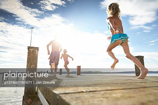 Kinder laufen über einen Steg, Starnberger See, Oberbayern, Bayern, Deutschland - p1316m1161071 von Jan Greune
