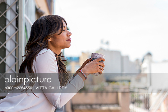 Female entrepreneur having coffee in balcony at office - p300m2264550 by VITTA GALLERY