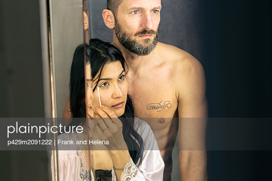 Semi-naked hipster couple looking into mirror in bathroom - p429m2091222 by Frank and Helena