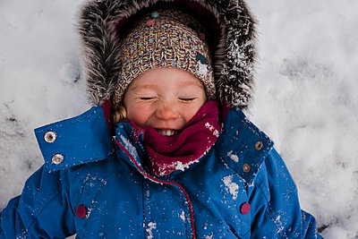 High angle view of smiling girl with eyes closed lying on snow covered field - p1166m1530801 by Cavan Images