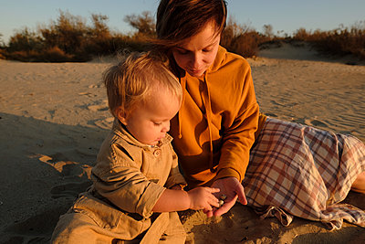 Woman with baby playing on beach - p1363m2142801 by Valery Skurydin