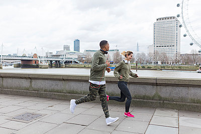 UK, London, man and woman running at riverwalk - p300m1120587f by Boy photography