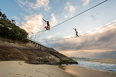 Man and woman slacklining and waterlining during sunrise in Leblon Beach, Rio de Janeiro, Brazil - p343m1543669 by Vitor Marigo