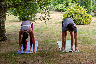 Man and woman practicing yoga in garden, bending forward - p429m2032200 by Image Source