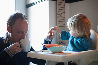 Toddler and uncle having cereal for breakfast in the kitchen; Toronto, Ontario, Canada - p442m936265 by Marina Dempster