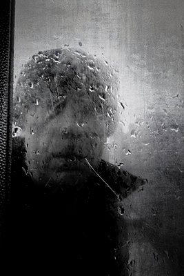 Man looking through dirty glass window - p597m793874 by Tim Robinson