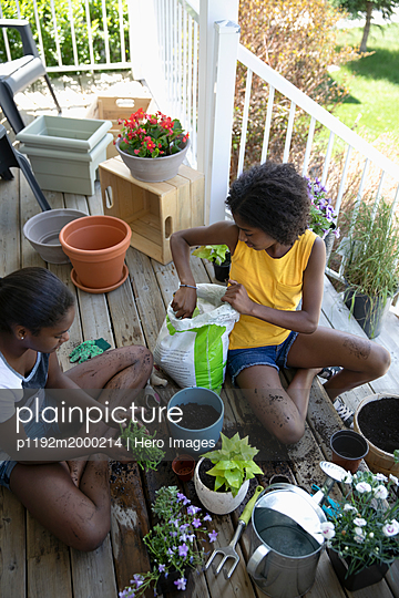 Tween sisters potting plants and flowers on front stoop - p1192m2000214 by Hero Images