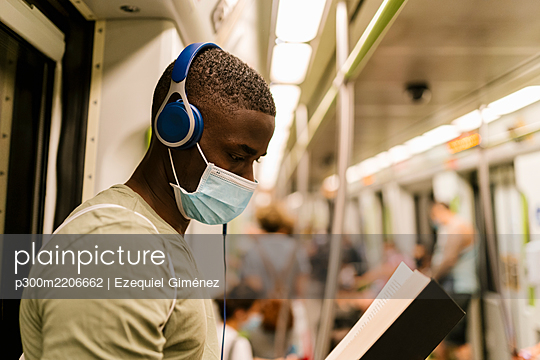 Close-up of young man wearing mask reading book and listening music through headphones in train - p300m2206662 by Ezequiel Giménez