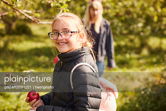 Girl picking apples from tree - p924m2091221 by heshphoto